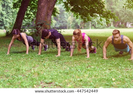 Two young couple working out in a park doing push-ups together in a row as they enjoy their daily workout - stock photo