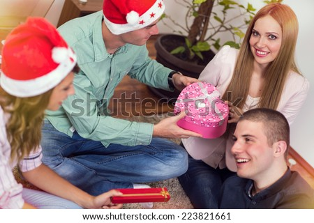Two young couples celebrating Christmas eve and exchanging presents - stock photo