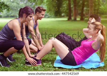 Two young couples doing sit ups in the park with one couple holding down the feet of the second man and woman as they work out in a healthy lifestyle concept - stock photo