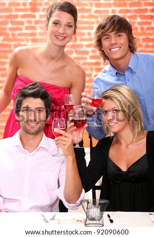 Two young couples drinking wine in restaurant - stock photo