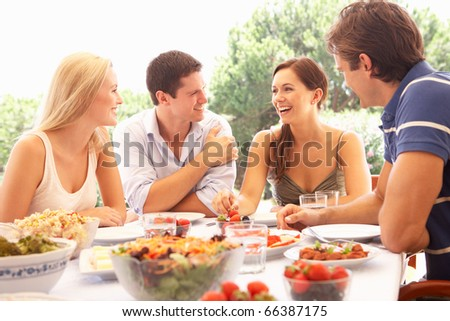 Two young couples eating outdoors - stock photo