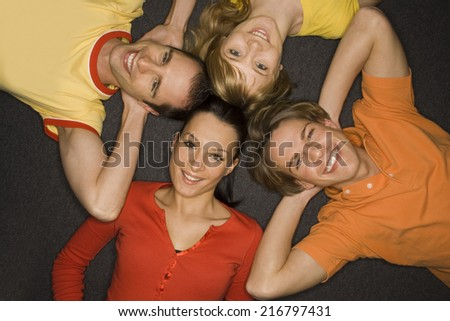 Two young couples lying down and smiling