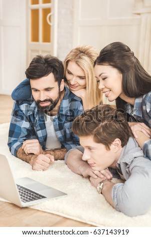 Two young couples lying on floor, having fun and using laptop