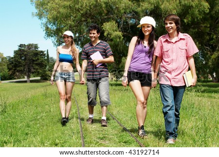 Two young couples of students going along a railroad line - stock photo