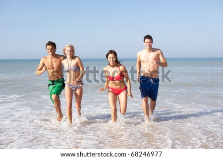 Two young couples on beach holiday - stock photo