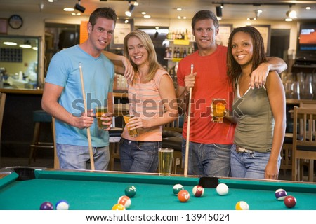 Two young couples standing beside a pool table in a bar