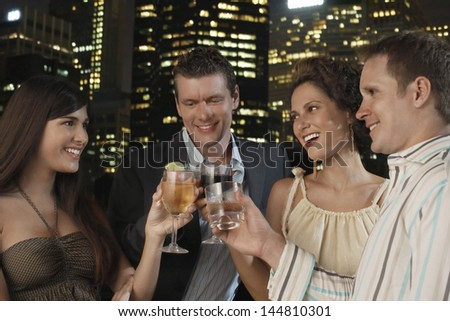Two young couples toasting drinks against city skyline at night - stock photo