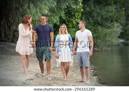 two young couples walking along the river relaxing in the beautiful nature - stock photo
