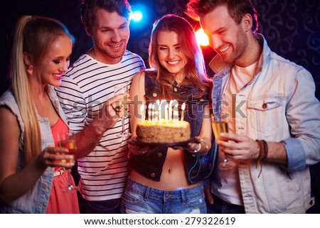 Two young couples with champagne and cake looking at candles at birthday party - stock photo