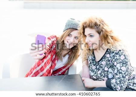 Two young curly and straight blonde hair caucasian woman sitting on a bar, using smart phone taking a selfie - technology, social network, communication concept