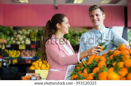 Two young customers buying oranges, lemons and tangerines in grocery section