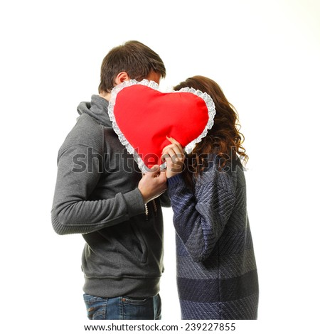 Two young dates kissing behind heart. on a white background - stock photo