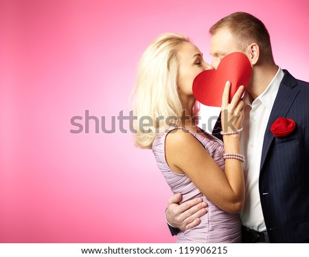 Two young dates kissing behind paper heart - stock photo