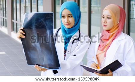 Two young doctors examining a file in in front of hospital - stock photo