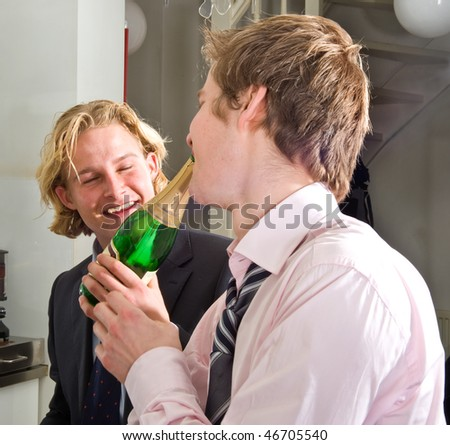two young, drunken adults drinking champagne - stock photo
