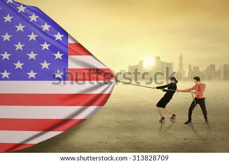 Two young entrepreneur try to pull a big american flag, shot outdoors - stock photo