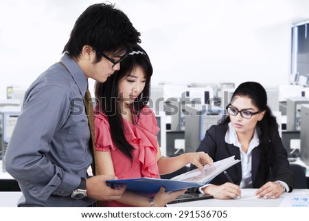 Two young entrepreneurs discussing a business document while their friend working on desk. Concept of busy businesspeople - stock photo