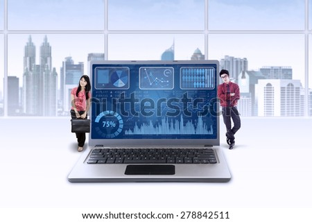 Two young entrepreneurs lean on laptop with financial chart grow upward - stock photo