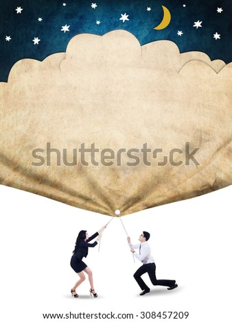 Two young entrepreneurs work together to pull a banner with stars and moon, symbolizing their hopes to success - stock photo