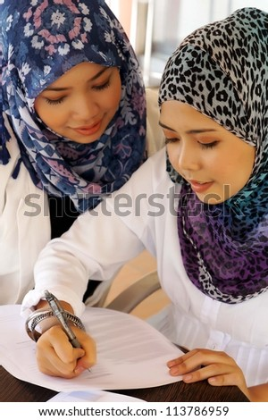 Two young executives signing document - stock photo