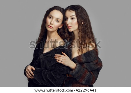 two young fashion angels in eco fur coat posing. perfect healthy skin. red lips. - stock photo