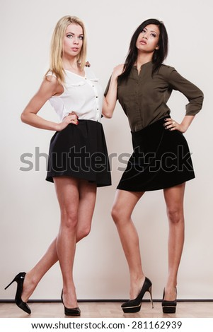 Two young fashion women caucasian and african in trendy short black skirts posing in full length studio portrait