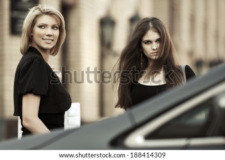Two young fashion women on the car parking - stock photo