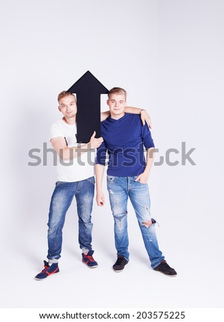 Two young fashionable man posing in studio with black empty arrow,looking at camera, smiling. Conceptual photo.