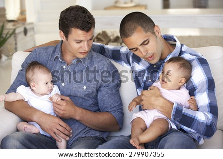 Two Young Fathers On Sofa At Home - stock photo