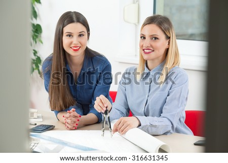 Two young female architects working on their design in an office
