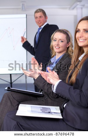 Two Young female clapp their hands during presentation, in the background young male presents something on the flipchart - stock photo