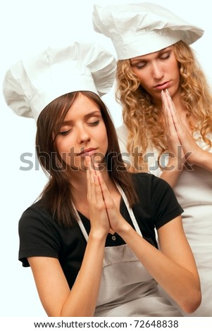 Two young female cookers praying, studio shot