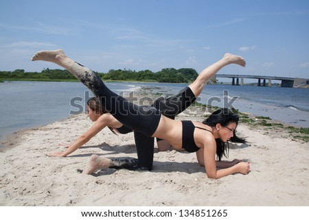 two young female doing yoga on the beach - stock photo