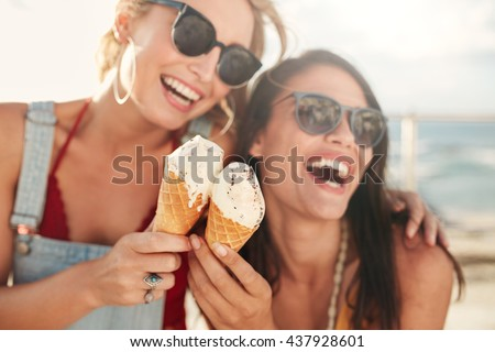Two young female friends having fun and eating ice cream. Cheerful young women eating icecream outdoors. - stock photo