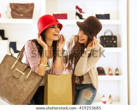 Two young female friends in a shopping,Trying hats and making fun. - stock photo