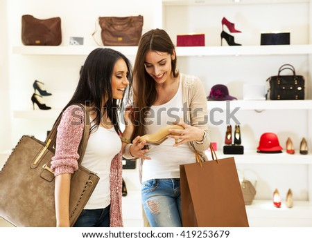 Two young female friends in a shopping,Trying shoes and making fun. - stock photo