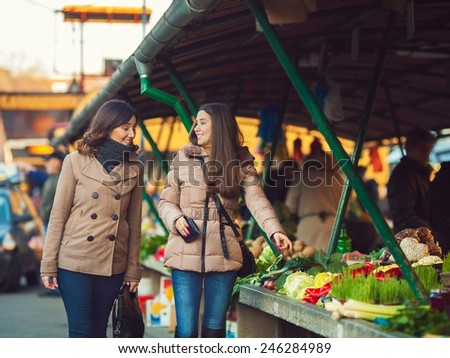 Two young female friends looking for some organic food at the market - stock photo