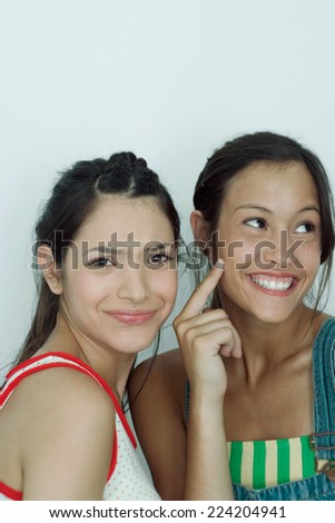 Two young female friends, one furrowing brow at camera, the other pointing to cheek, looking away, portrait - stock photo