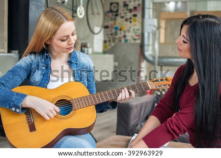 Two young female friends. One girl playing guitar and the other one listening. - stock photo