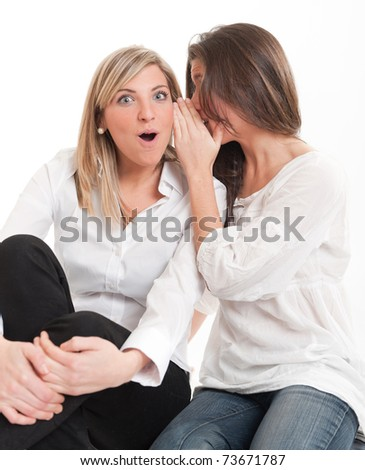 Two young female friends one whispering on the other?s ear - stock photo