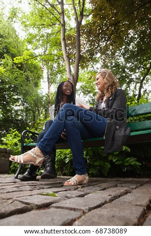 Two young female friends sitting on bench in the park and chatting