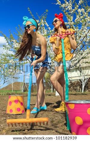 Two young female raking soil on garden - stock photo