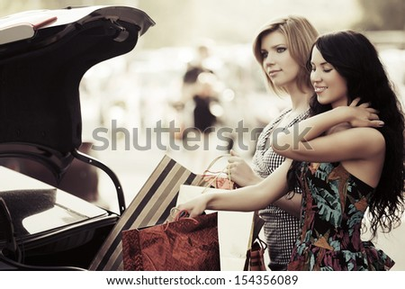 Two young female shoppers at the car  - stock photo