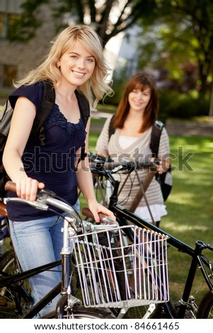 Two young female students with bikes on a university campus - stock photo