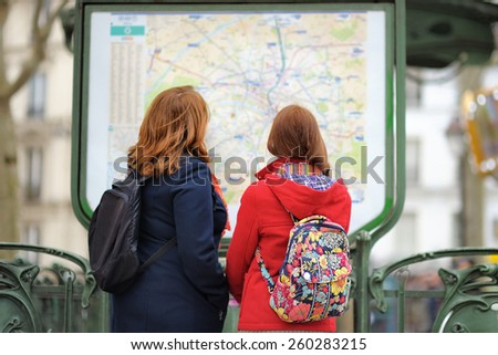 Two young female tourist looking at the map of Parisian metro - stock photo