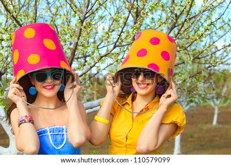 Two young female with buckets on their heads on garden