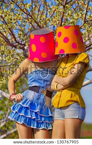 Two young female with buckets on their heads on garden - stock photo