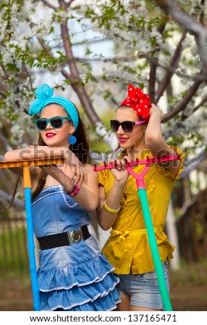 Two young female with rakes on garden   - stock photo