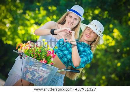 Two young females on bike making heart shape with their hands. Beauty, nature and love concepts. - stock photo