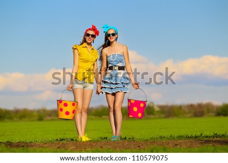 Two young females with  buckets on garden - stock photo